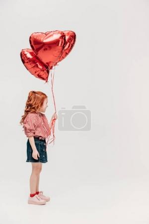 adorable redhead child holding red heart shaped balloons isolated on grey