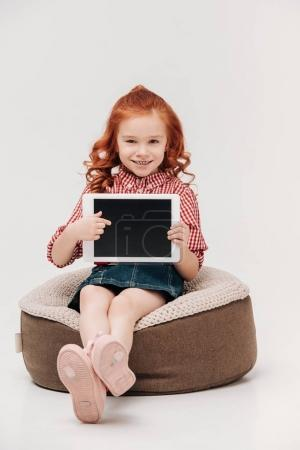 adorable redhead child smiling at camera and pointing at digital tablet with blank screen isolated on grey