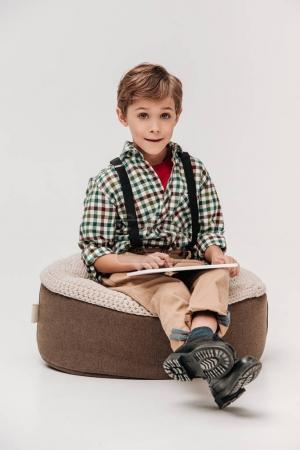 cute little boy using digital tablet and smiling at camera isolated on grey