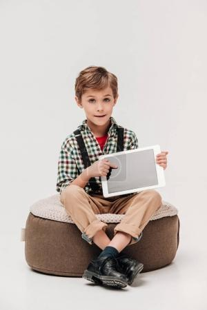 cute little boy showing digital tablet with blank screen and looking at camera isolated on grey