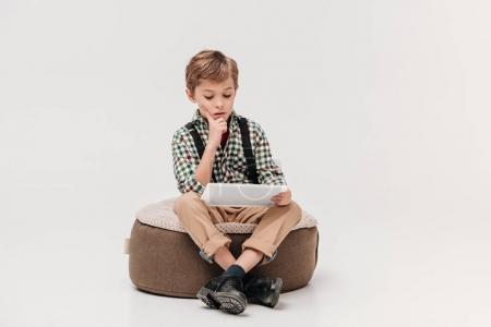 Photo pour Petit garçon concentré assis et utilisant tablette numérique isolé sur gris - image libre de droit