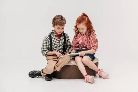beautiful little kids using digital tablet together isolated on grey