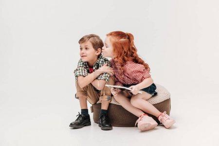 Photo pour Adorable petite fille tenant tablette numérique et capable d'embrasser petit garçon isolé sur gris - image libre de droit