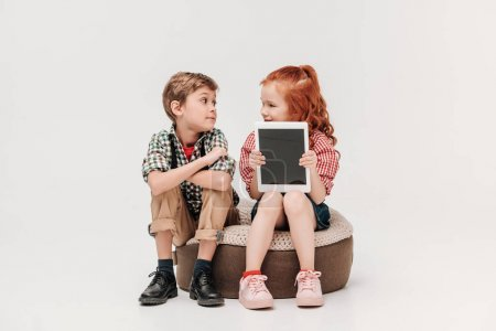 beautiful kids looking at each other and showing digital tablet with blank screen isolated on grey