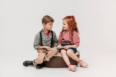 adorable children smiling each other while using digital tablet isolated on grey