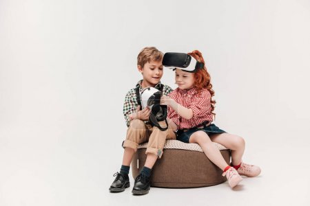 beautiful little kids using virtual reality headsets isolated on grey