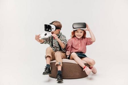 adorable happy kids using virtual reality headsets isolated on grey