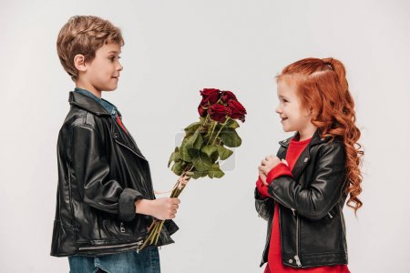 side view of little boy presenting roses bouquet to his girlfriend isolated on grey