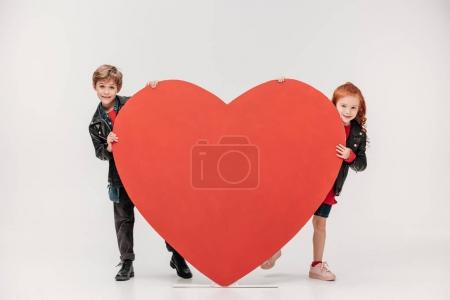 funny little kids couple hiding behind large red heart isolated on grey