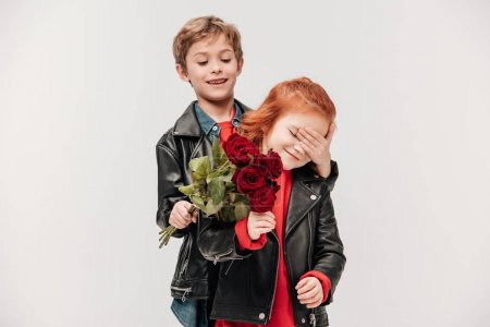 happy boy presenting roses bouquet to his little girlfriend isolated on grey