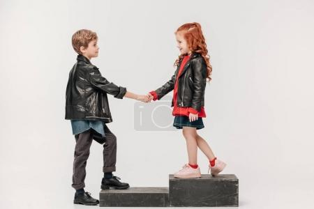 stylish little kids couple holding hands on stairs isolated on grey