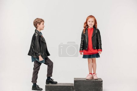 adorable little kids couple on stairs isolated on grey