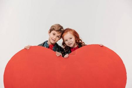 happy bonding little kids behind large red heart isolated on grey