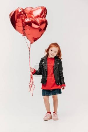 adorable little girl with balloons in shape of hearts isolated on grey