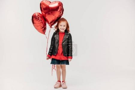 Photo for Happy little girl with balloons in shape of hearts isolated on grey - Royalty Free Image