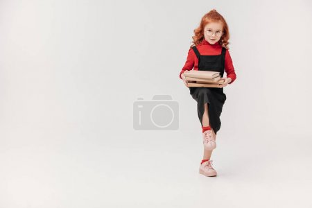 adorable little schoolgirl carrying stack of books isolated on grey