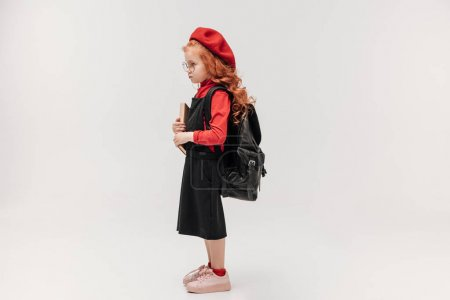 side view of adorable little schoolgirl in red beret with book and backpack isolated on grey