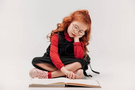 adorable little schoolgirl reading book while sitting on floor isolated on grey
