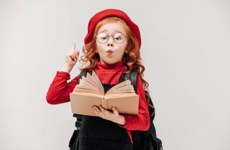 Photo pour Petite écolière ayant idée tout en lisant livre isolé sur gris - image libre de droit