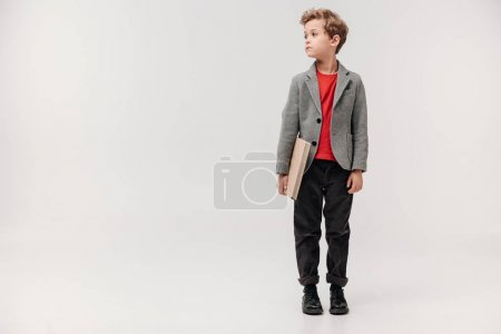 Photo for Stylish little schoolboy with big book isolated on grey - Royalty Free Image
