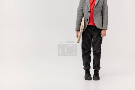 cropped shot of stylish little schoolboy with big book isolated on grey
