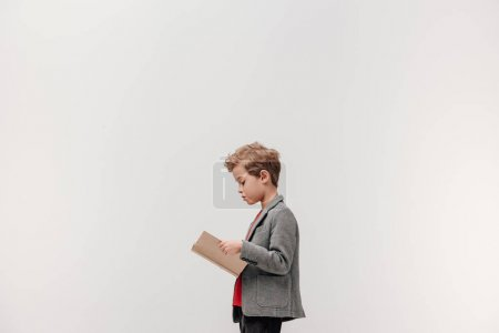 Photo for Side view of stylish little schoolboy reading book isolated on grey - Royalty Free Image