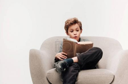 Photo for Excited little schoolboy reading book in armchair isolated on grey - Royalty Free Image