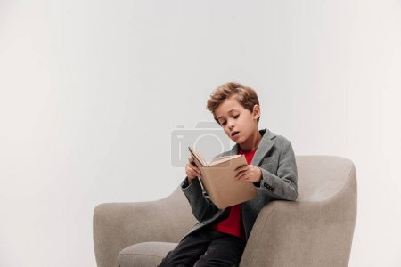 focused little schoolboy reading book in armchair isolated on grey