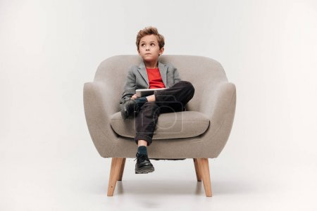 stylish little boy sitting in armchair with digital tablet
