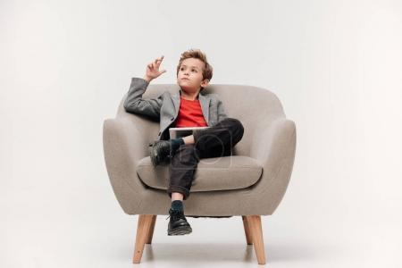 thoughtful stylish little boy sitting in armchair with tablet