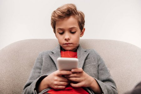 serious little boy using smartphone while sitting in armchair isolated on grey