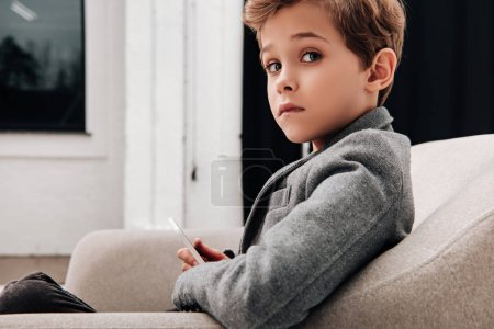 elegante pequeño muchacho sentado en cómodo sillón y con smartphone
