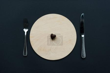 top view of heart shaped chocolate candy on round board with cutlery isolated on black