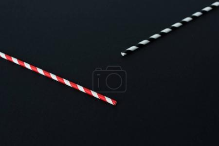 close-up view of striped drinking straws isolated on black