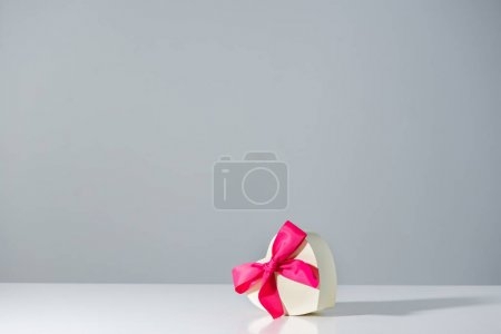 heart shaped gift box with pink ribbon on grey