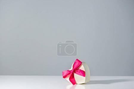 Foto de Corazón en forma de caja de regalo con cinta rosa en gris - Imagen libre de derechos
