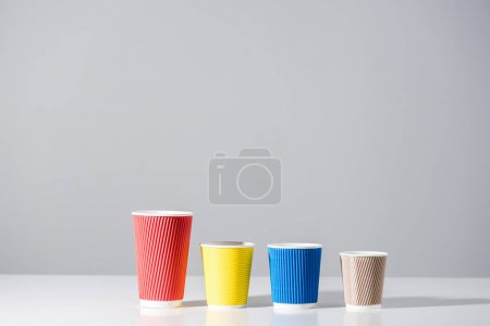 various colored paper cups in a row on grey