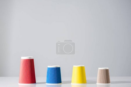 various colorful paper cups in a row on grey