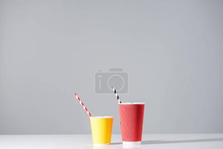 red and yellow paper cups with drinking straws on grey