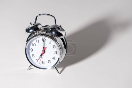 close-up view of shiny alarm clock with shadow on grey