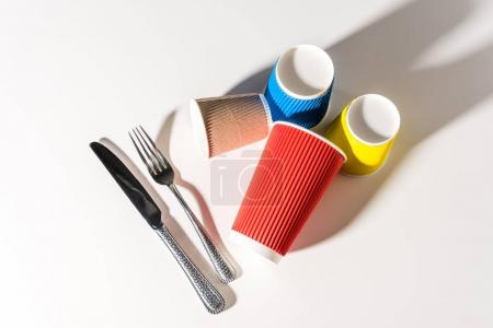 top view of colorful paper cups and cutlery on white