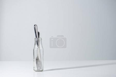 fork and knife in glass bottle with shadow on grey