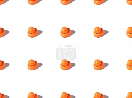 seamless pattern of small orange rubber ducks toys on white