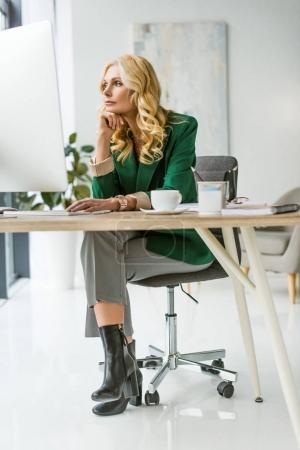 Photo pour Attrayante femme âgée moyenne utilisant l'ordinateur de bureau au lieu de travail - image libre de droit