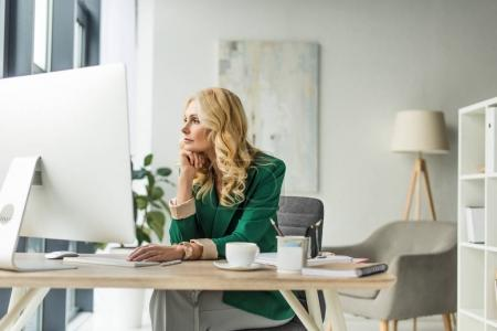 Photo for Pensive businesswoman looking away while using desktop computer at workplace - Royalty Free Image