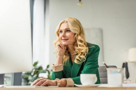 smiling middle aged businesswoman using desktop computer at workplace