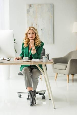 middle aged businesswoman using desktop computer and looking at camera at workplace