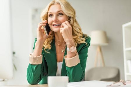 smiling middle aged businesswoman talking by smartphone at workplace