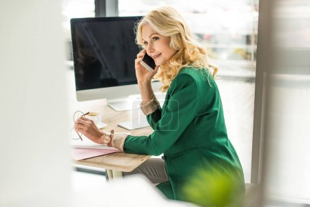selective focus of beautiful businesswoman talking by smartphone at workplace