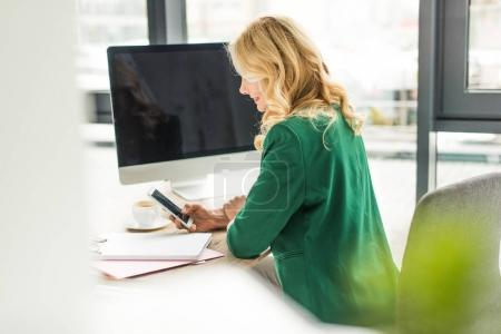 selective focus of businesswoman using smartphone at workplace
